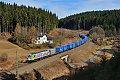 Foto zeigt: Bunte Lok mit blauen Kisten im braunen Frankenwald